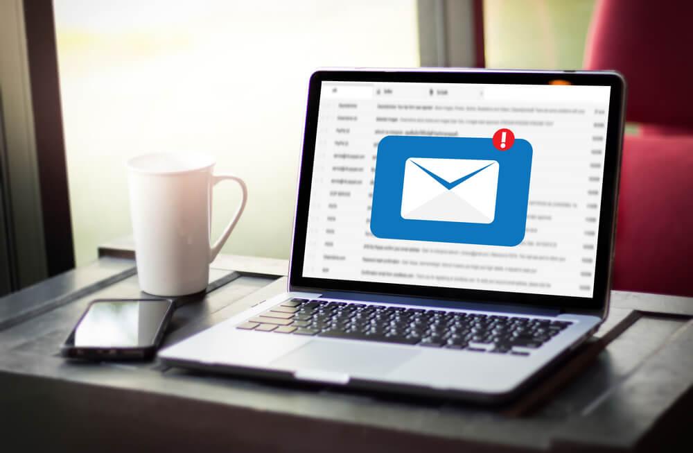 laptop em site de email em mesa ao lado de xicara de cafe e smartphone