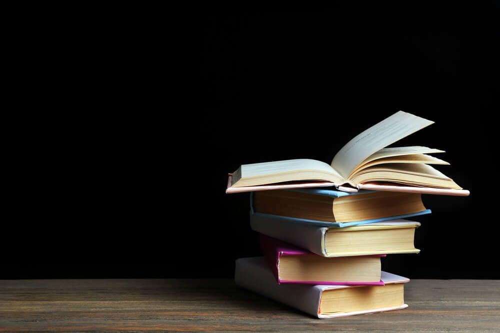 livros empilhados em mesa com fundo preto