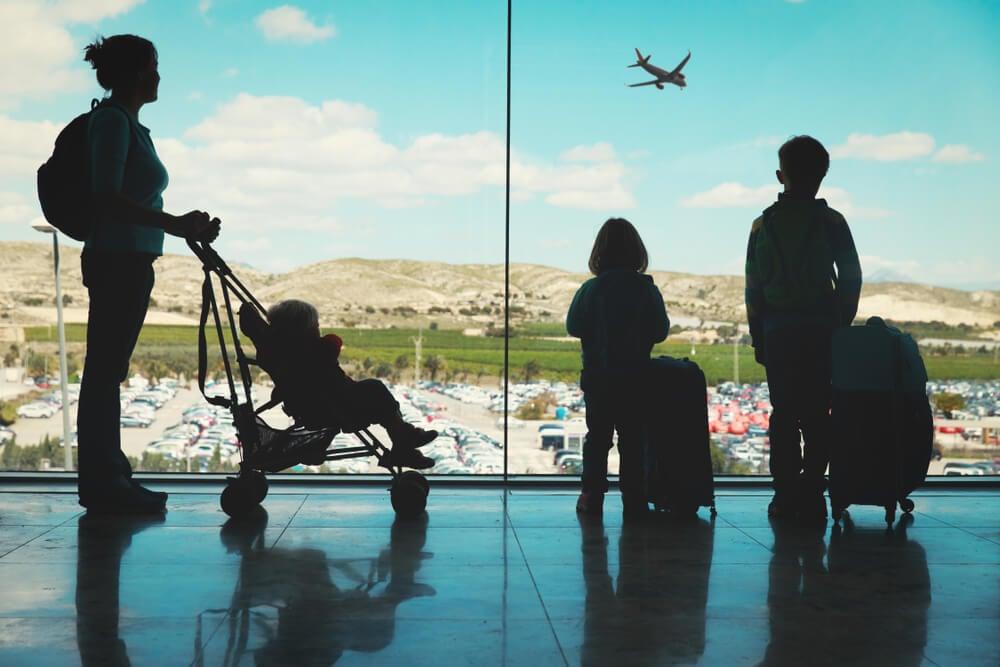mae e filhos com malas em viagem em familia