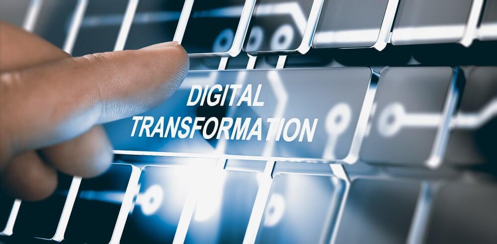 mão assinalando botão luminoso com título transformação digital