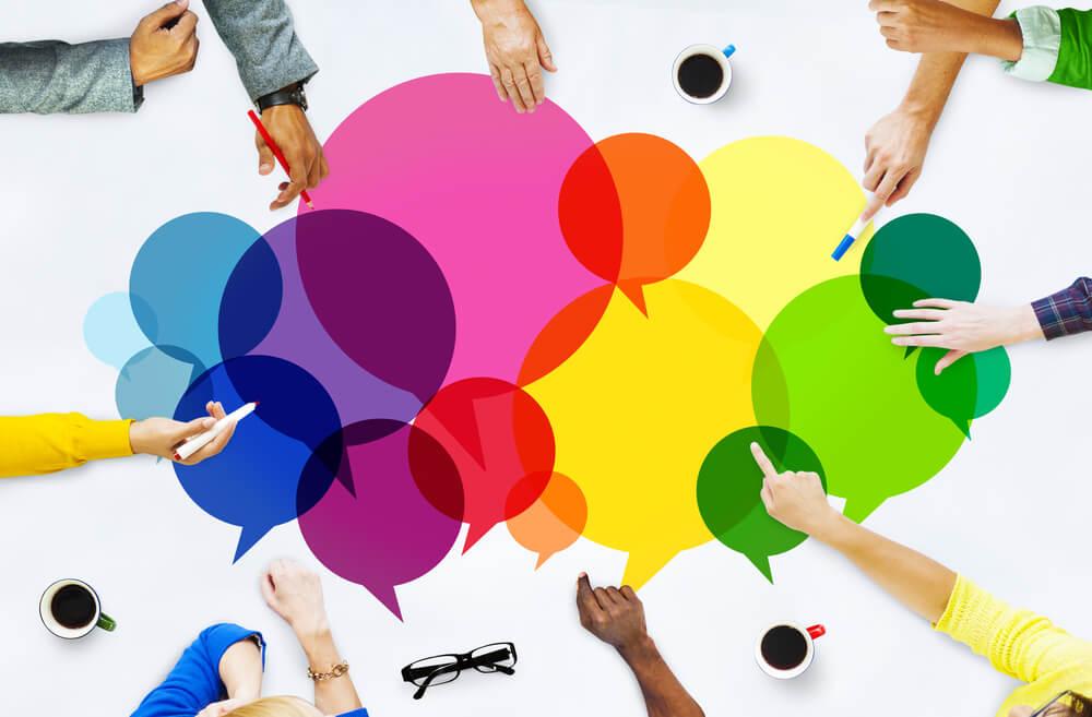 mão em mesa de reunião com balões de comunicação
