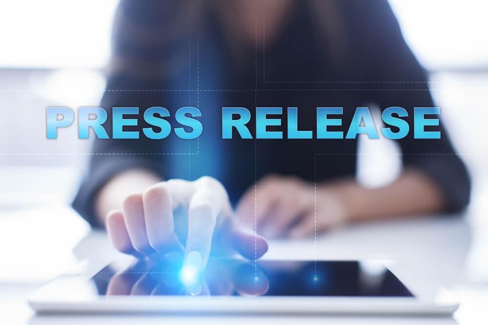 mão feminina acessando tablet e título luminoso press release