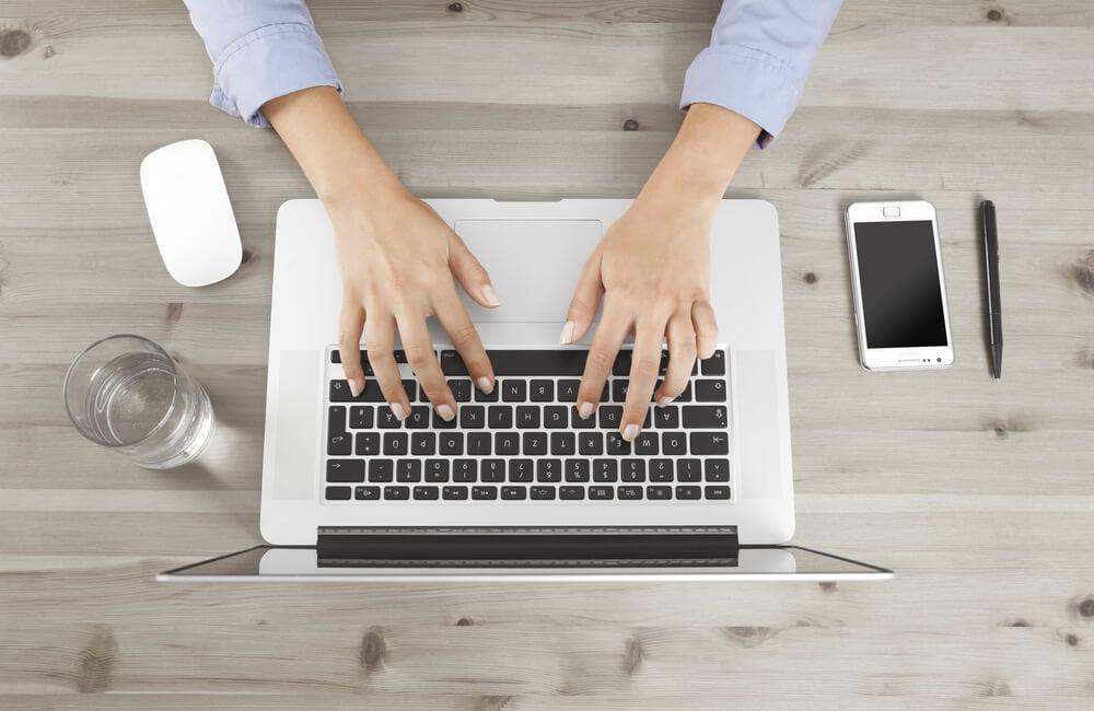 mao feminina em laptop com smartphone, caneta e copo ao lado