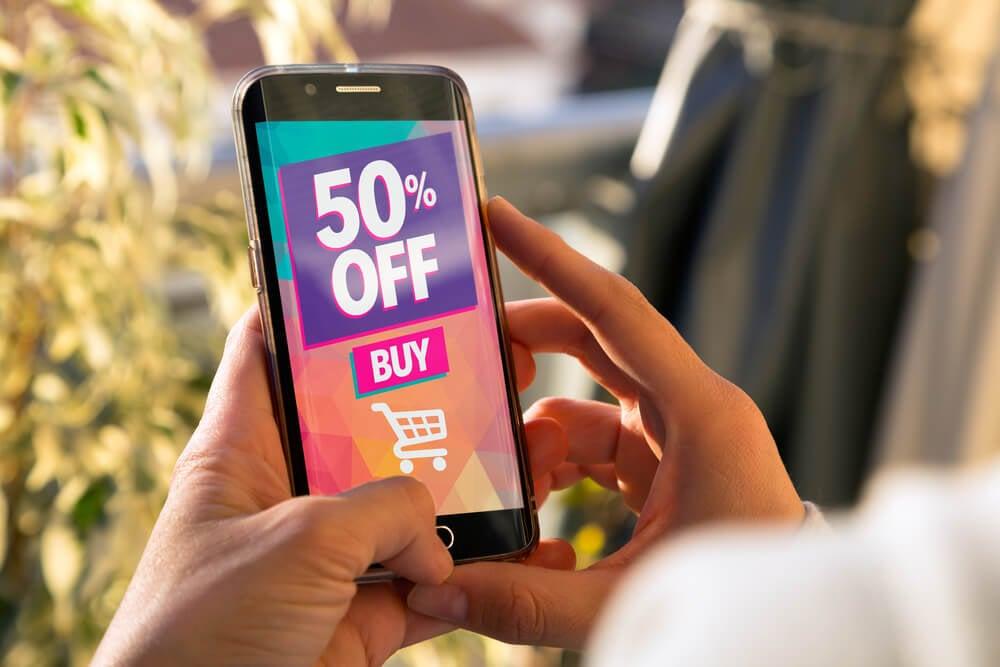 mao feminina segurando smartphone com desconto de produtos em tela