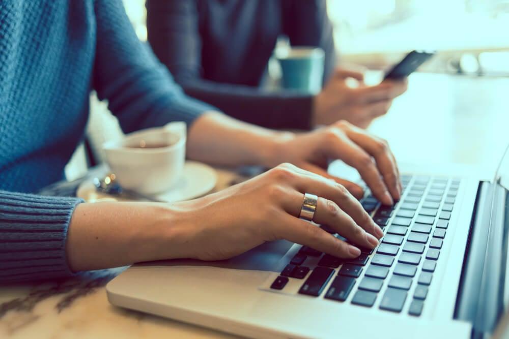 mao feminina teclando em laptop com xicara de cafe ao lado