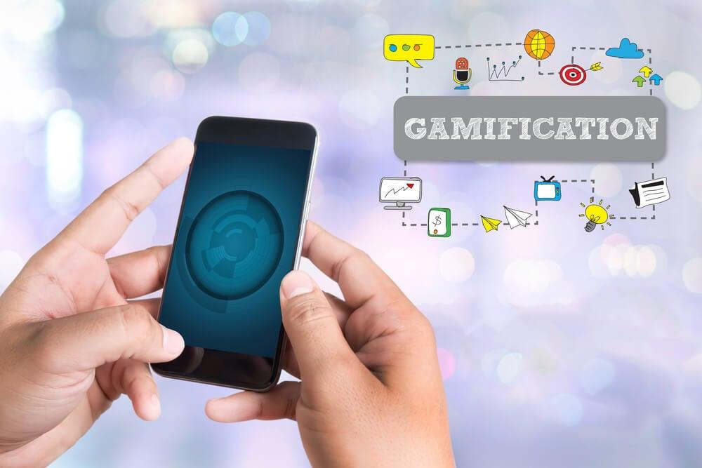 mão masculina acessando smartphone e ilustração de título gamificação e símbolos relacionados