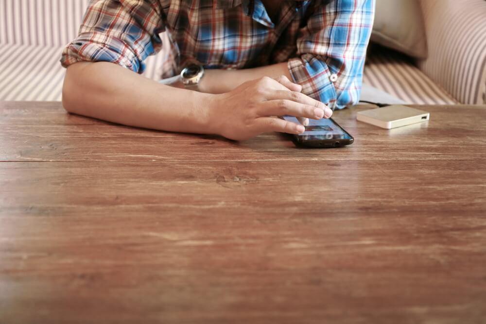 mão masculina acessando smartphone em mesa de madeira