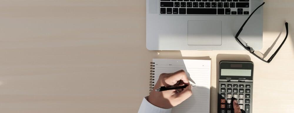 mao masculina calculando ticket medio e escrevendo em bloco de notas em frente a laptop