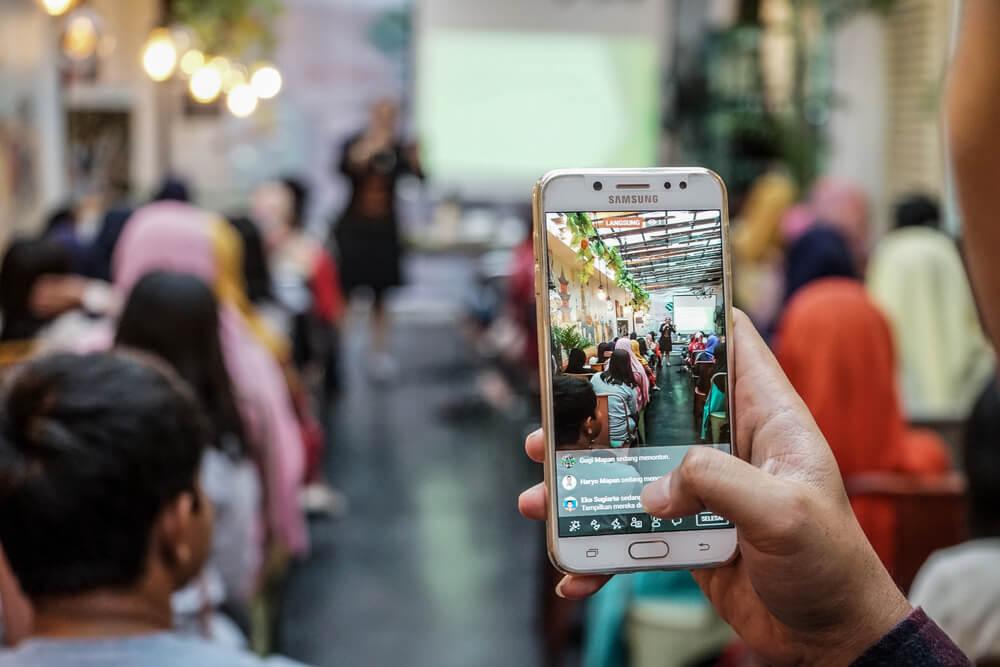 mao masculina com smartphone gravando evento