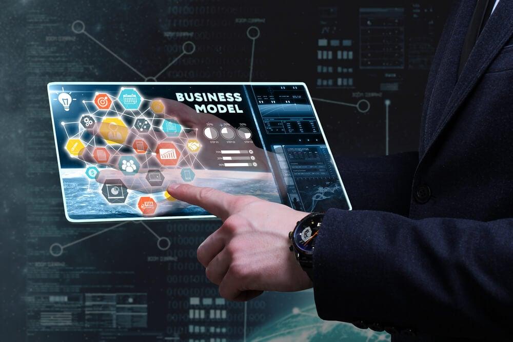 mão masculina de executivo assinalando título de modelo de negócio em tablet