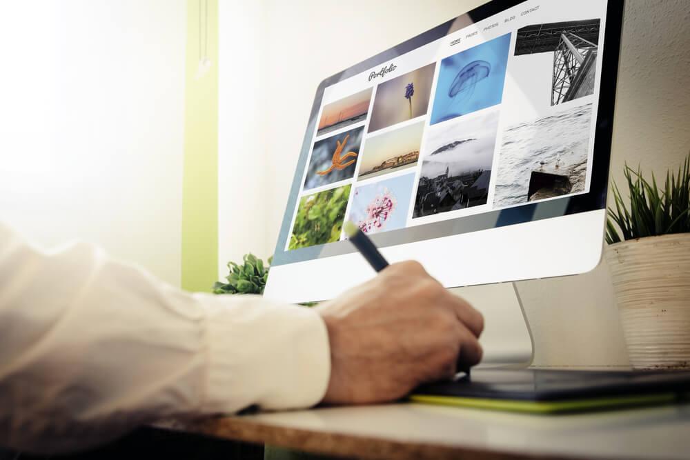 mão masculina em caneta e desktop com tela de acesso a plataforma de portfolio online