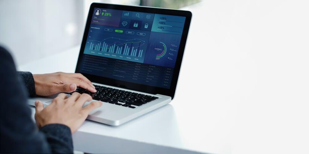 mao masculina em frente a laptop com estatisticas em tela