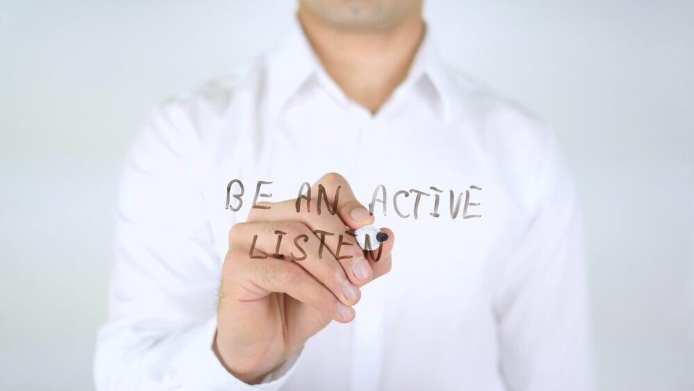 mão masculina escrevendo frase seja um ouvinte ativo