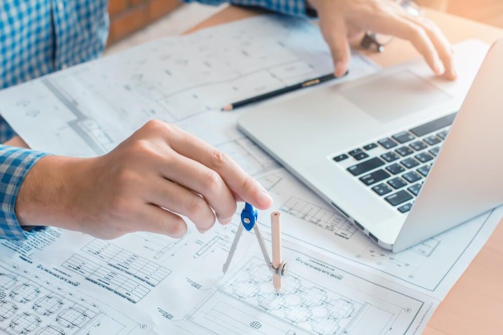 mao masculina segurando compasso em folhas de planejamentos e laptop ao lado simbolizando arquitetura da informaçao