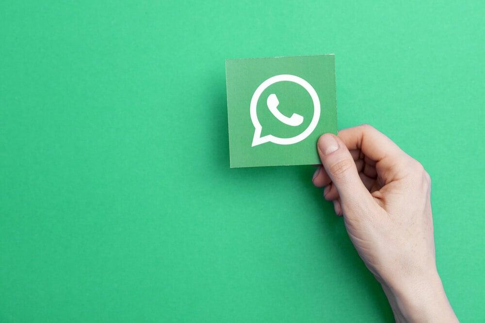 mao masculina segurando folha com icone do aplicativo whatsapp em fundo verde