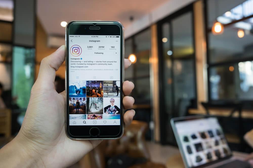 mao masculina segurando smartphone em perfil do aplicativo instagram em meio a local publico