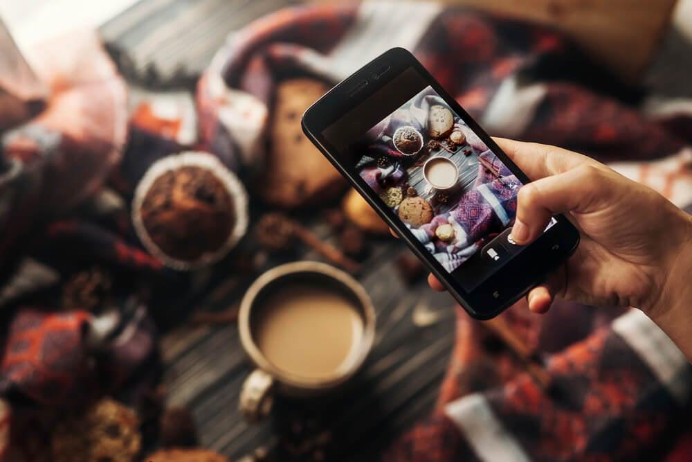 mao masculina segurando smartphone tirando foto de uma xicara de cafe