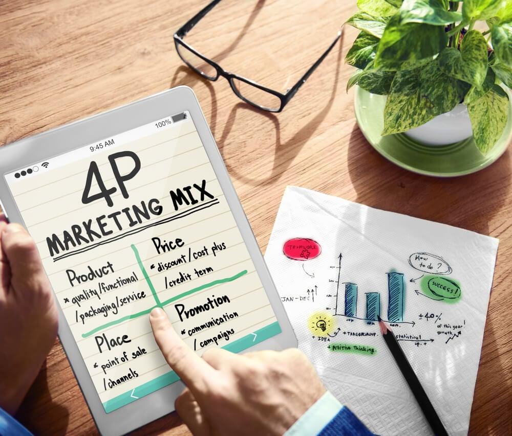 mão masculina segurando tablet com títulos dos 4ps principais do marketing digital