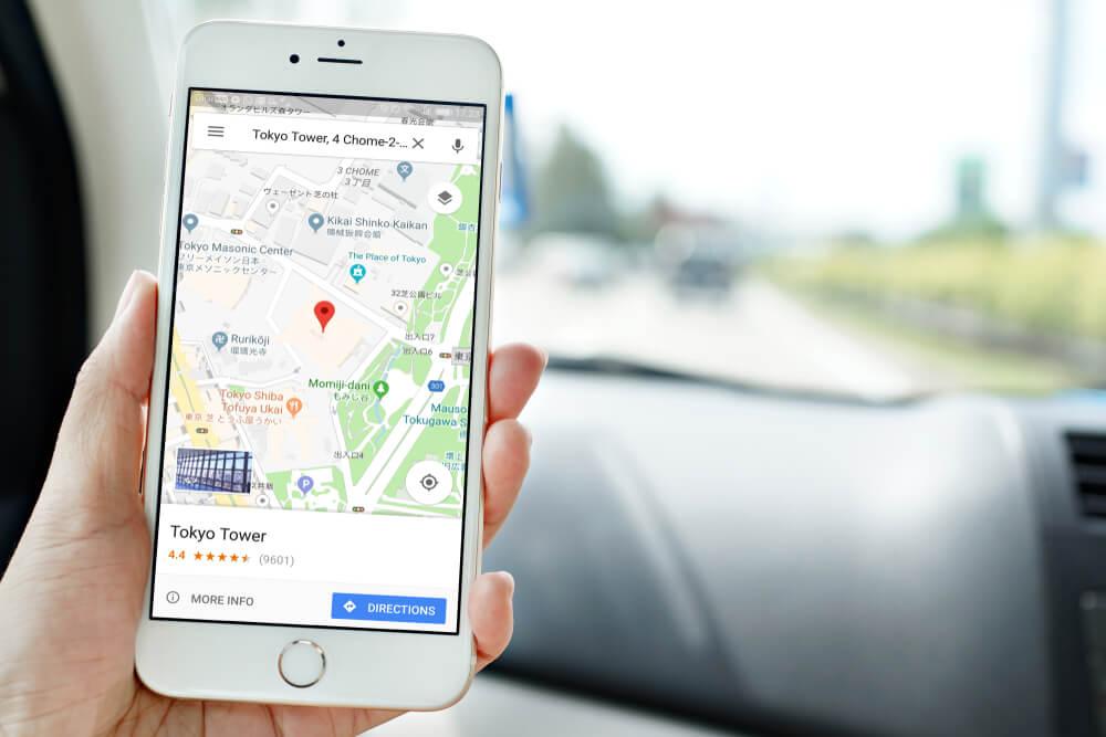 mão segurando smartphone acessando Google Maps