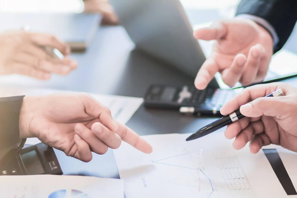 mãos de equipe executiva discutindo sobre graficos e cálculos