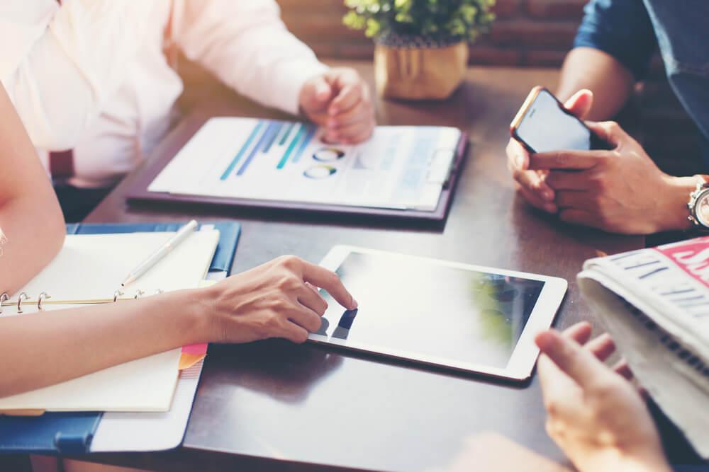 mãos de pessoas de equipe analisando e criando gráficos e cronogramas em tablet sob mesa