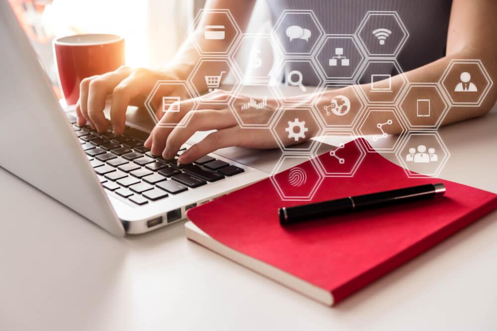 maos femininas em teclado de laptop com bloco de notas e xicara de cafe ao lado e ilustraçao de simbolos de marketing
