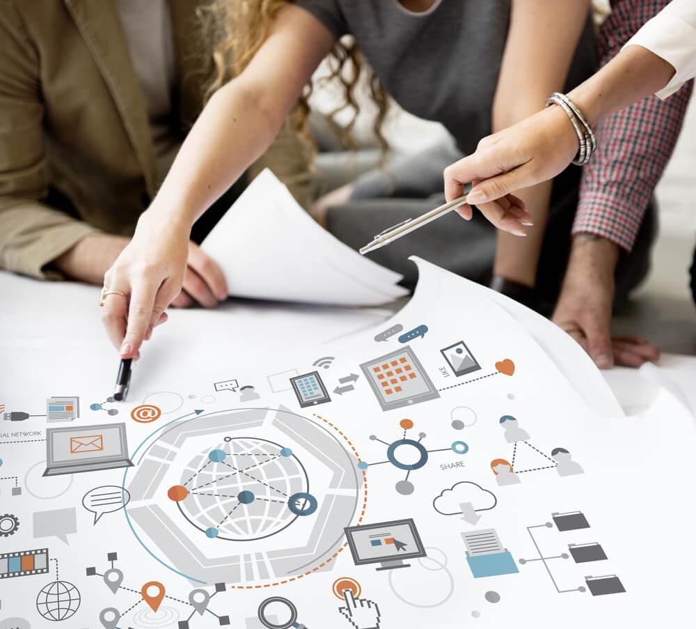 maos femininas indicando locais em folha de planejamento tecnologico