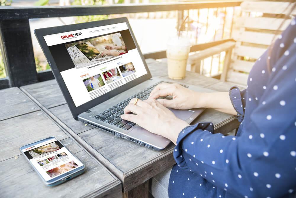 maos femininas teclando em laptop com site em tela e smartphone ao lado