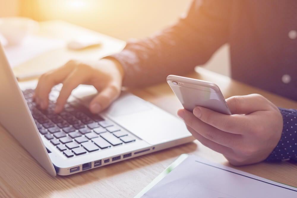 maõs masculinas acessando smartphone e laptop