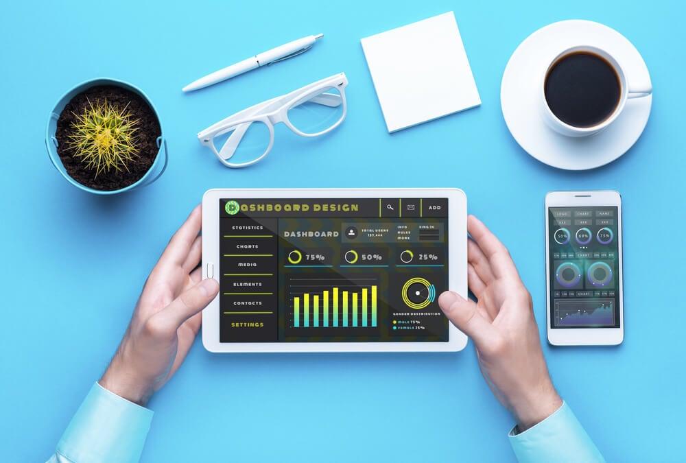 mãos masculinas segurando tablet com dados junto de smartphone e itens de mesa de escritório