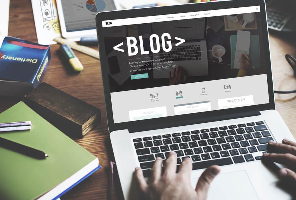 maos masculinas teclando em laptop em mesa de escritorio com a palavra blog em tela