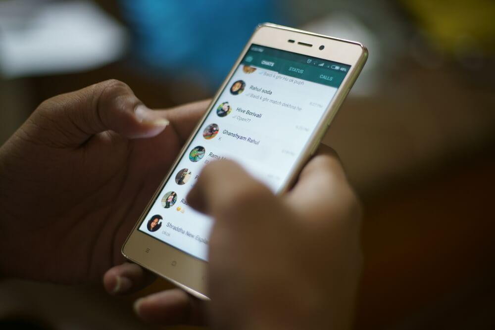 maos segurando smartphone em tela de conversas whatsapp