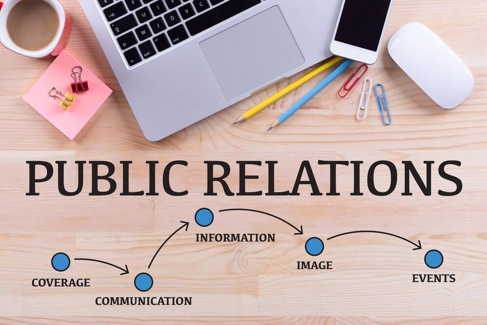 mesa com laptop e materiais de escritorio com a frase public relations e palavras relacionadas