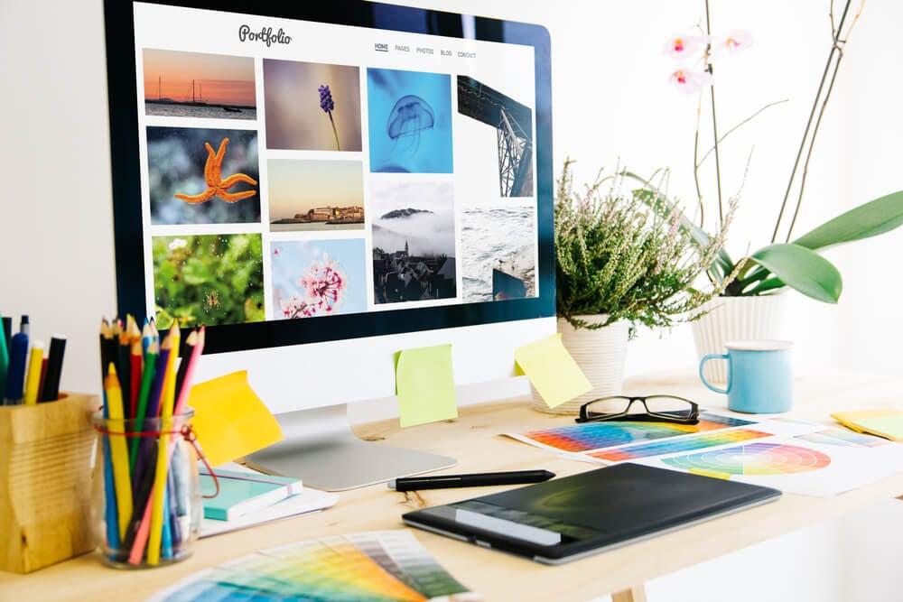 mesa de escritório informal com desktop acessando página de portfolios online