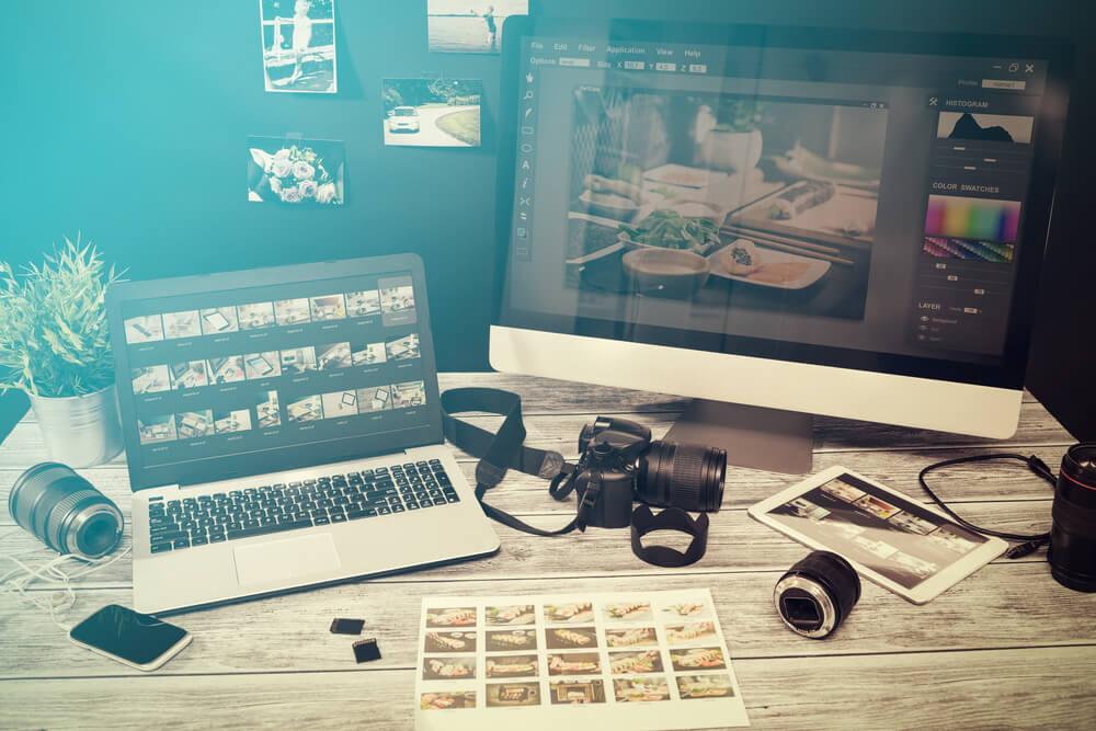 mesa de profissional da fotografia e tela de desktop acessando banco de imagens