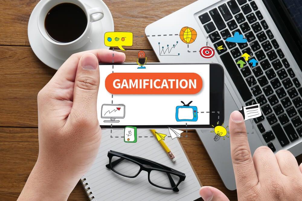 mesa de trabalho com laptop smartphone e símbolos relacionados a gamificação