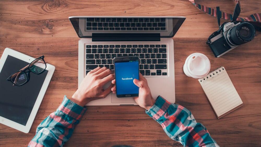 mesa de trabalho e homem acesasndo facebook no smartphone