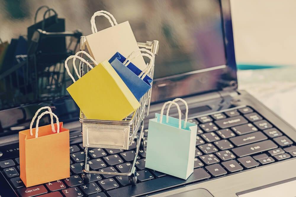 mini carrinho de compras e sacolas em laptop