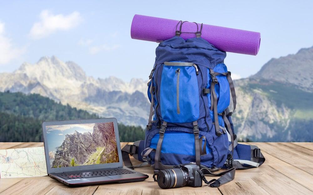 mochila de viajante, camera e laptop em cenario de montanhas