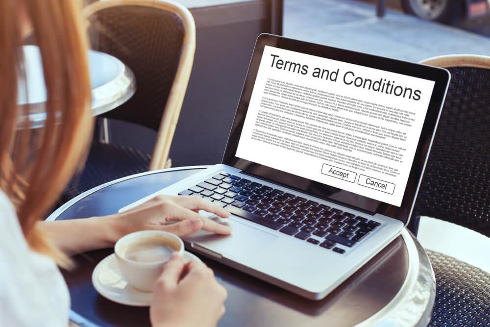 mulher acessando laptop segurando xícara de café com termos e condições na tela