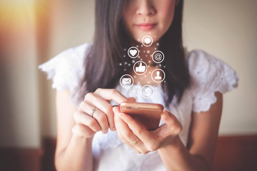 mulher acessando smartphones e redes sociais que fazem parte do processo de marketing 4.0