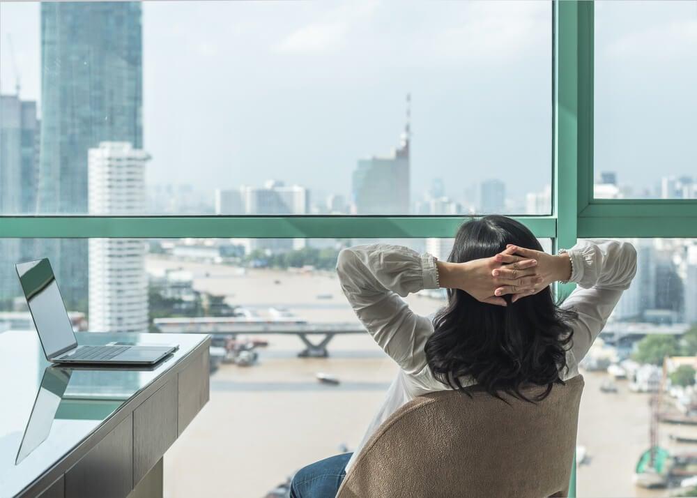 mulher com as mãos na cabeça em posição de descanso em frente a computador e paisagem