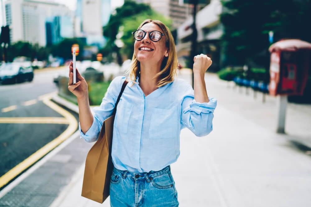mulher com expressão de comemoração segurando smartphone
