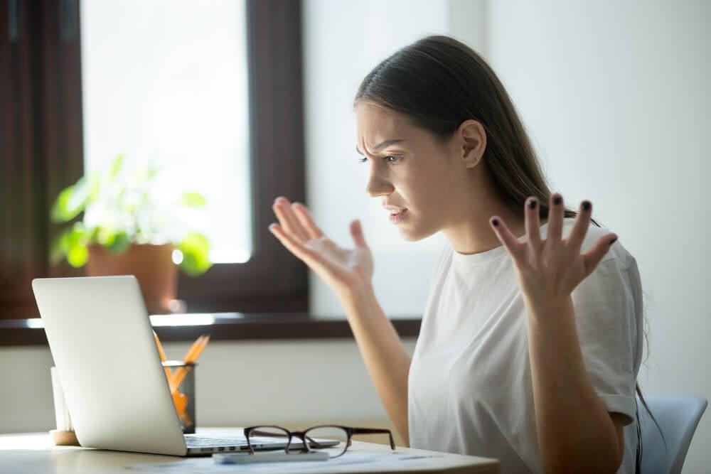 mulher com expressao raivosa em frente a laptop