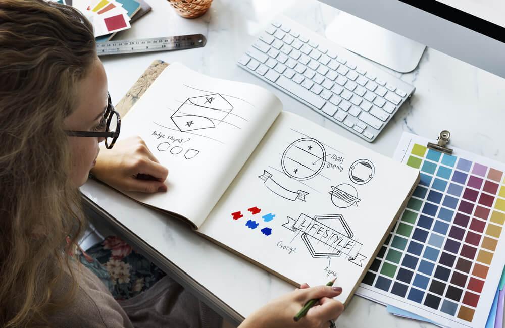 mulher em mesa de trabalho e rascunhos de logotipos criativos e manual de cores
