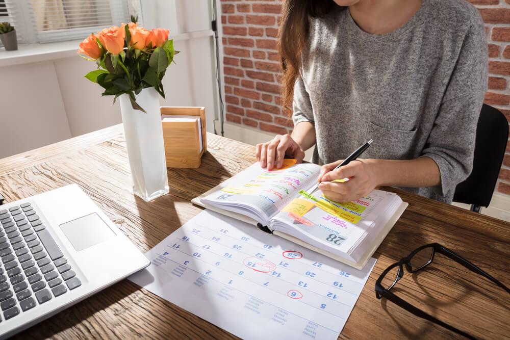 mulher fazendo anotações em agenda junto de calendario der planejamento