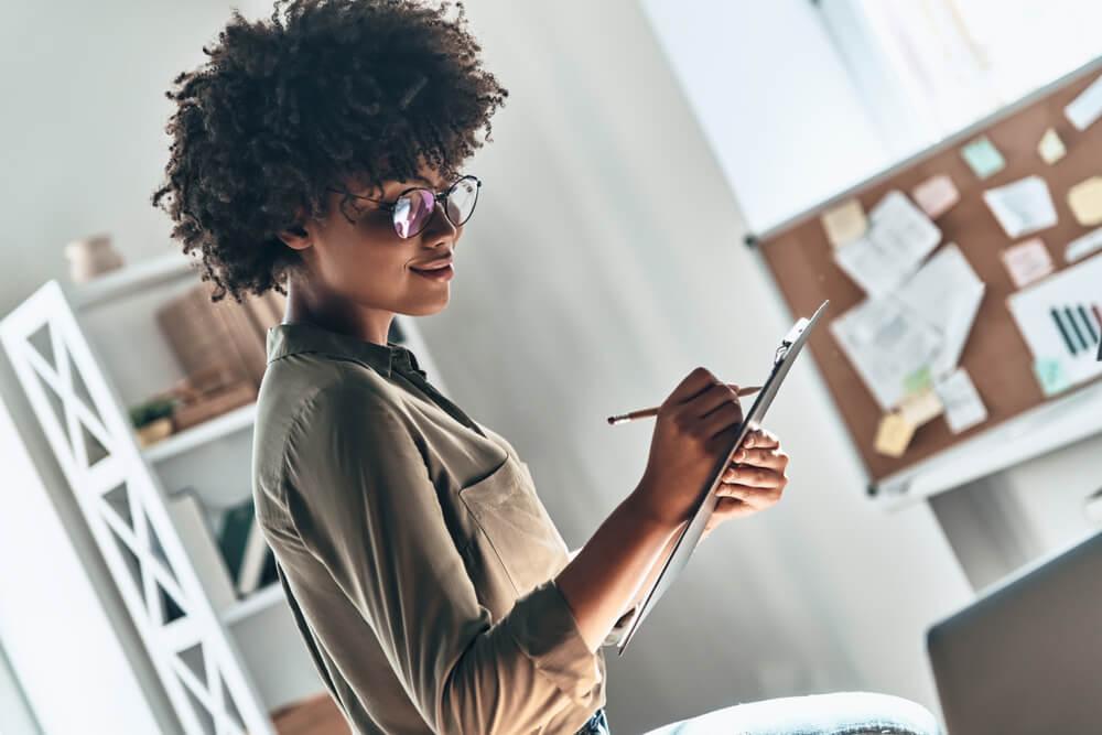 mulher fazendo anotações em prancheta