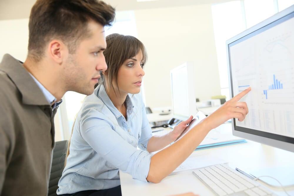 mulher mostrando estatisticas em tela de computador para colega de trabalho