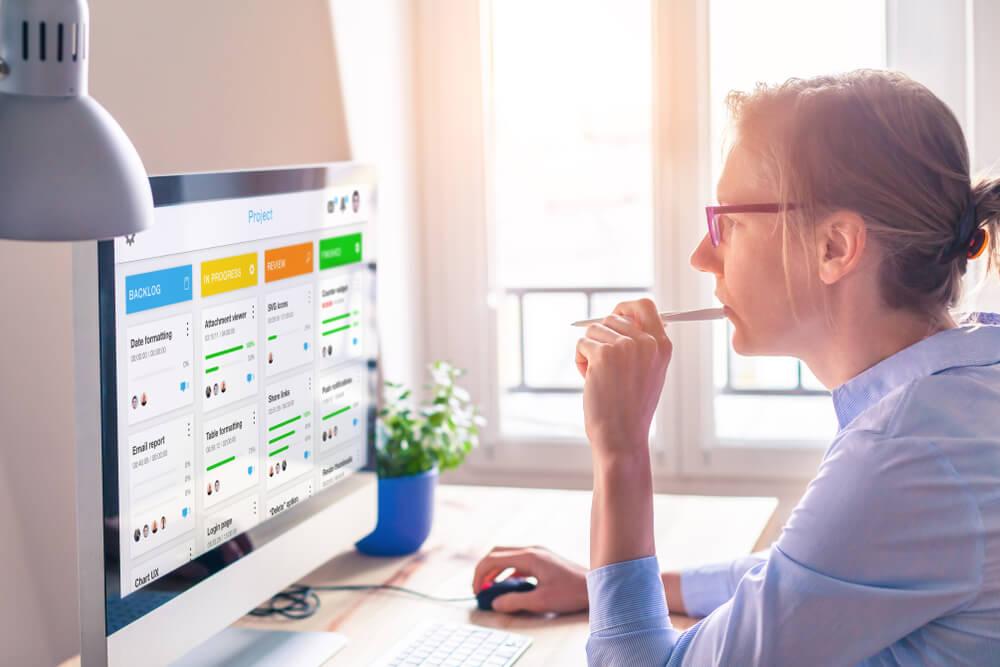 mulher profissional a frente de computador acessando metodologia agil de tarefas