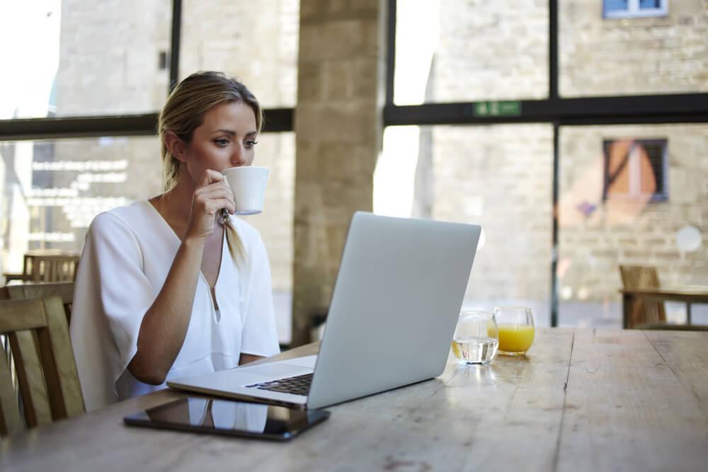 mulher profissional trabalhando remotamente enquanto toma café